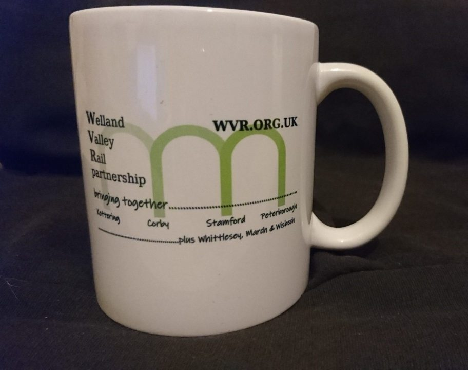 Welland Valley Rail promotional mug. A white ceramic mug, with three outline arches representative of the shape of the Welland viaduct of the logo in green. Text reads: Welland Valley Rail partnership, bringing together Kettering, Corby, Stamford, Peterborough plus Whittlesey, March Wisbech