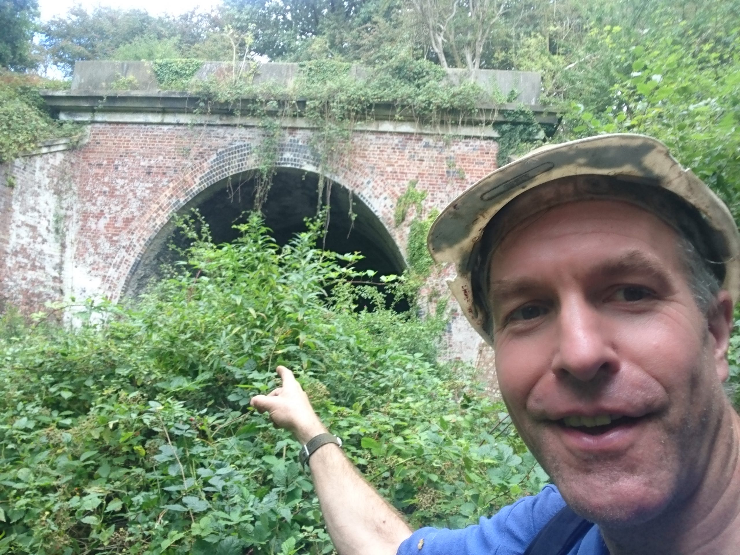 Team member Owen smiling and pointing at the tunnel portal which is heavily obstructed by overgrown bushes